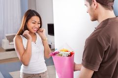 Woman receiving bouquet from delivery man Stock Photography