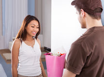 Woman Receiving Bouquet From Delivery Man Stock Photo