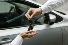 Woman receiving car key from man. Hand: woman receiving car key from man Royalty Free Stock Photos