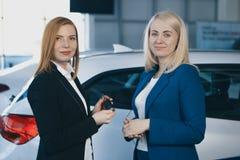 Woman receiving car keys from a dealer. Woman receiving car keys from a Royalty Free Stock Photos