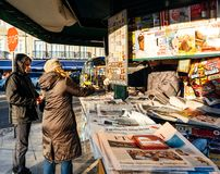 Woman receiving change at press kiosk buy newspaper. LISBON, PORTUGAL - FEB 10, 2018: Couple receiving change at press kiosk after buying fresh newspaper in Stock Photos