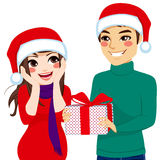 Woman Receiving Christmas Present. Woman surprised receiving Christmas present from man Stock Photo
