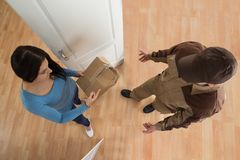 Woman receiving damaged package from delivery man Royalty Free Stock Photos