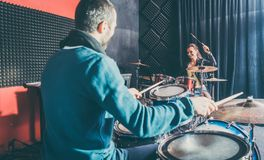 Woman receiving drum lessons from her music teacher royalty free stock photography