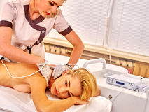 Woman receiving electricity gloves massage at beauty salon. Stock Photos