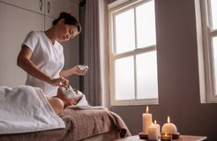 Woman receiving face mask treatment in spa. Woman receiving a face mask treatment in a beauty spa by therapist. Experienced cosmetician applying facial mask on Stock Photos