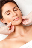 Woman receiving face massage Stock Photography