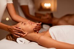 Woman Receiving Face Massage During Couples Therapy Lying In Spa
