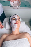 Woman receiving facial mask from beautician in spa Royalty Free Stock Photo