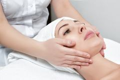Woman receiving facial massage at spa salon. Young beautiful woman receiving facial massage at spa salon stock photos