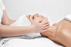 Woman receiving facial massage at spa salon. Young beautiful woman receiving facial massage at spa salon royalty free stock images