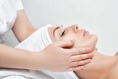 Woman receiving facial massage at spa salon. Young beautiful woman receiving facial massage at spa salon Royalty Free Stock Photo