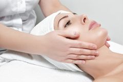 Woman receiving facial massage at spa salon. Young beautiful woman receiving facial massage at spa salon stock image