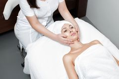 Woman receiving facial massage at spa salon. Young beautiful women receiving facial massage at spa salon royalty free stock image