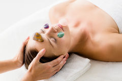 Woman receiving facial stone massage Royalty Free Stock Photography