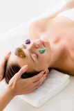 Woman receiving facial stone massage from masseur Stock Photography