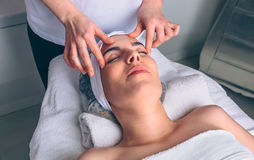 Woman receiving facial treatment on clinical center. Young women with closed eyes receiving facial massage on a clinical center. Medicine, healthcare and beauty Stock Photo
