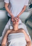 Woman receiving facial treatment on clinical center Stock Photo