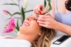 Woman receiving false eye lashes - beauty studio. Woman receiving false eye lashes in beauty studio Stock Images