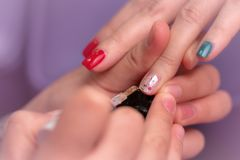 Woman receiving fingernail manicure service by professional manicurist at nail salon. Beautician painting nails at nail and spa. Salon. Focused on white and royalty free stock photo