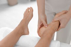Woman receiving foot massage in wellness center. Closeup royalty free stock photography