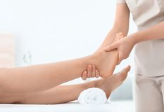 Woman receiving foot massage in wellness center. Closeup stock images