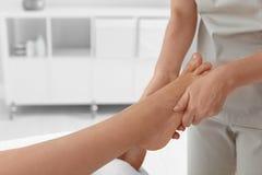 Woman receiving foot massage in wellness center. Closeup stock photography
