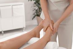 Woman receiving foot massage in wellness center. Closeup stock photos