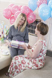 Woman Receiving Gift At Baby Shower. Happy blond women receiving gift from her mother at baby shower royalty free stock photography