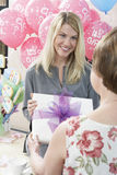 Woman Receiving Gift At Baby Shower. Happy blond women receiving gift from her mother at baby shower stock images
