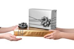 Woman receiving gift boxes from her friend. On white background Royalty Free Stock Photo