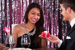 Woman receiving gift from man in restaurant Royalty Free Stock Images