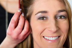 Woman receiving haircut in hairdressers shop. Hairdresser - hair stylist cutting hairs, a customer gets a haircut stock photo