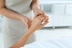 Woman receiving hand massage in wellness center. Closeup royalty free stock image