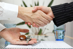 Woman receiving a handshake and a house key. At the same time Royalty Free Stock Image