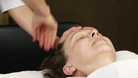 Woman receiving head massage at spa center. female doctor doing face massage. 4K. Woman receiving head massage at spa center. female doctor doing face massage stock video