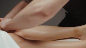 Woman receiving health body massage procedure in spa. Masseur doing leg massage.