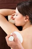Woman Receiving Herbal Massage With Stamps At Spa. Directly above shot of relaxed woman receiving herbal massage with stamps at beauty spa stock photo