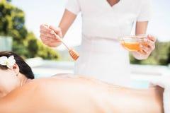 Woman receiving a honey massage from masseur Stock Image