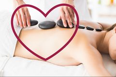 Woman receiving hot stone back massage in spa Royalty Free Stock Images
