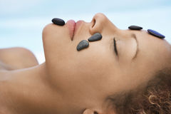 Woman Receiving Hot Stone Therapy On Face. Closeup of woman receiving hot stone therapy on face Stock Image