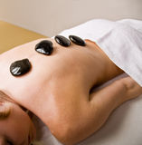 Woman receiving hot stone therapy massage Stock Photos