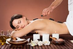 Woman receiving hot stone therapy in spa Stock Image