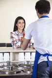 Woman Receiving Ice Cream From Waiter At Counter Royalty Free Stock Photos