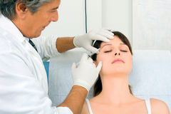 Woman receiving an injection of botox from a doc Stock Image