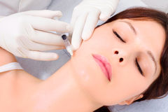 Woman receiving an injection of botox from a docto stock image