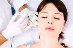 Woman receiving an injection of botox from a docto Royalty Free Stock Images