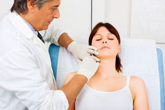 Woman receiving an injection of botox from a docto. Young caucasian women receiving an injection of botox from a doctor Royalty Free Stock Photos