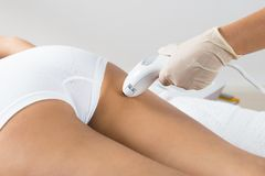 Woman receiving laser treatment on buttock. Close-up Of Woman Lying Receiving Epilation Laser Treatment On Buttock royalty free stock photos