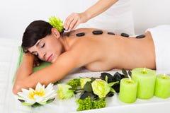 Woman Receiving Lastone Massage. Beautiful Woman Relaxing At A Spa Receiving Hot Stone Massage stock photo